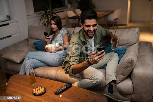 493656728 istock photo Young couple spend their evening at home using a smartphone 1043828712
