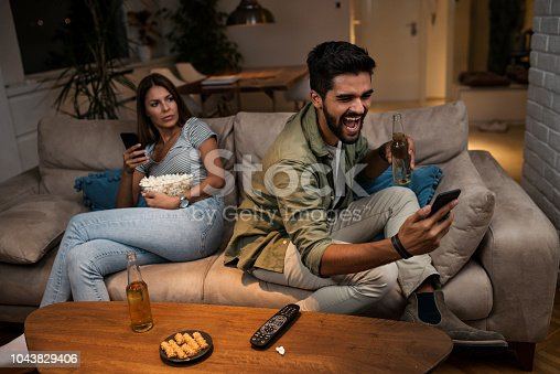 493656728 istock photo Young couple spend their evening at home using a smartphone 1043829406