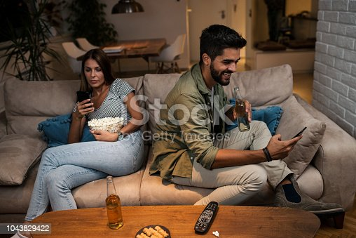 493656728 istock photo Young couple spend their evening at home using a smartphone 1043829422