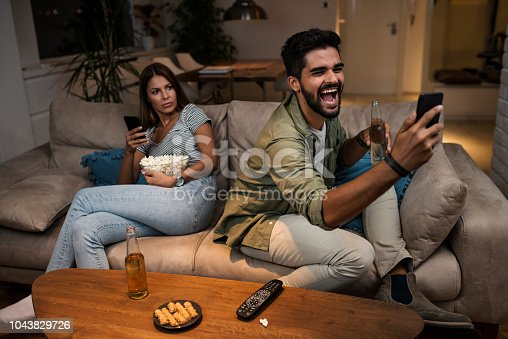 493656728 istock photo Young couple spend their evening at home using a smartphone 1043829726
