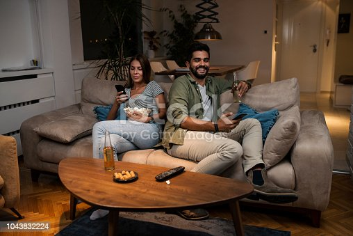 493656728 istock photo Young couple spend their evening at home using a smartphone 1043832224