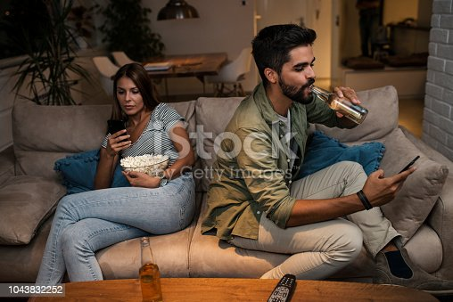 493656728 istock photo Young couple spend their evening at home using a smartphone 1043832252