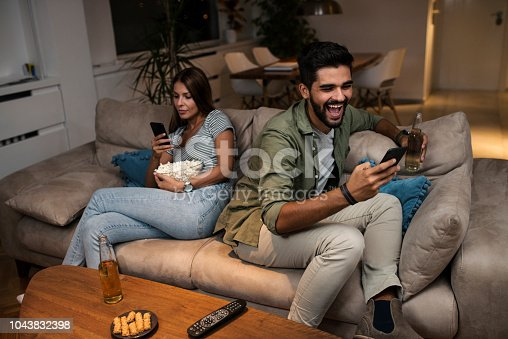 493656728 istock photo Young couple spend their evening at home using a smartphone 1043832398