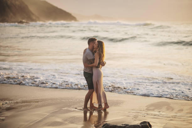 Young couple spending time together by the sea stock photo