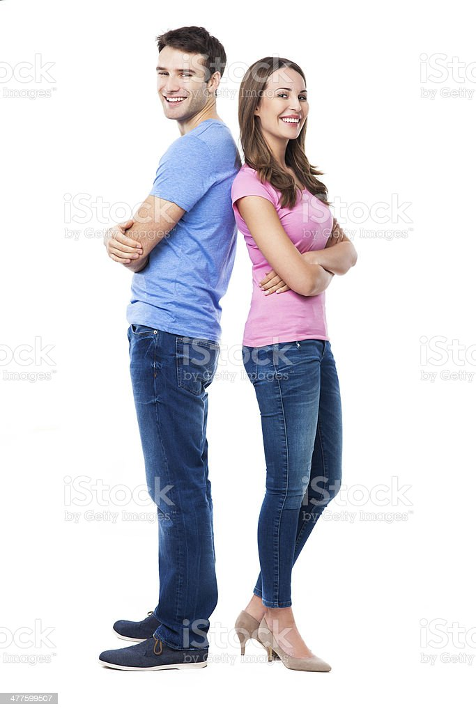 Young couple standing back to back stock photo