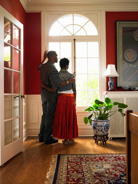 Young couple standing by window in living room stock photo