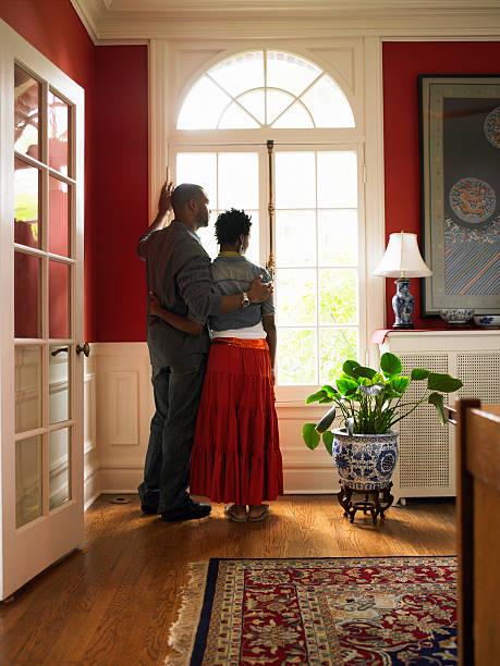 Junges Paar stehend durch Fenster im Wohnzimmer – Foto