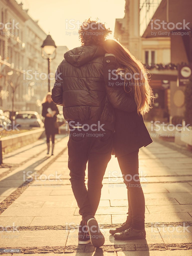 Young couple standing embraced on the street stock photo
