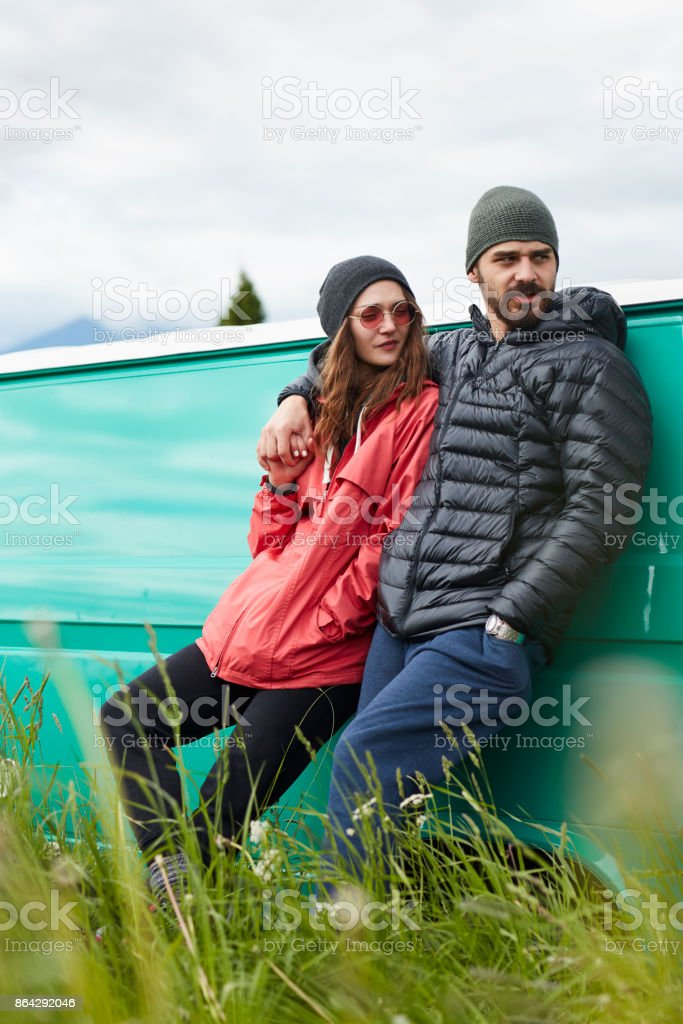 Young couple standing in front of camper royalty-free stock photo