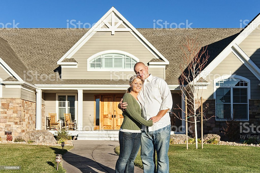 Young Couple Standing in front of New Home stock photo