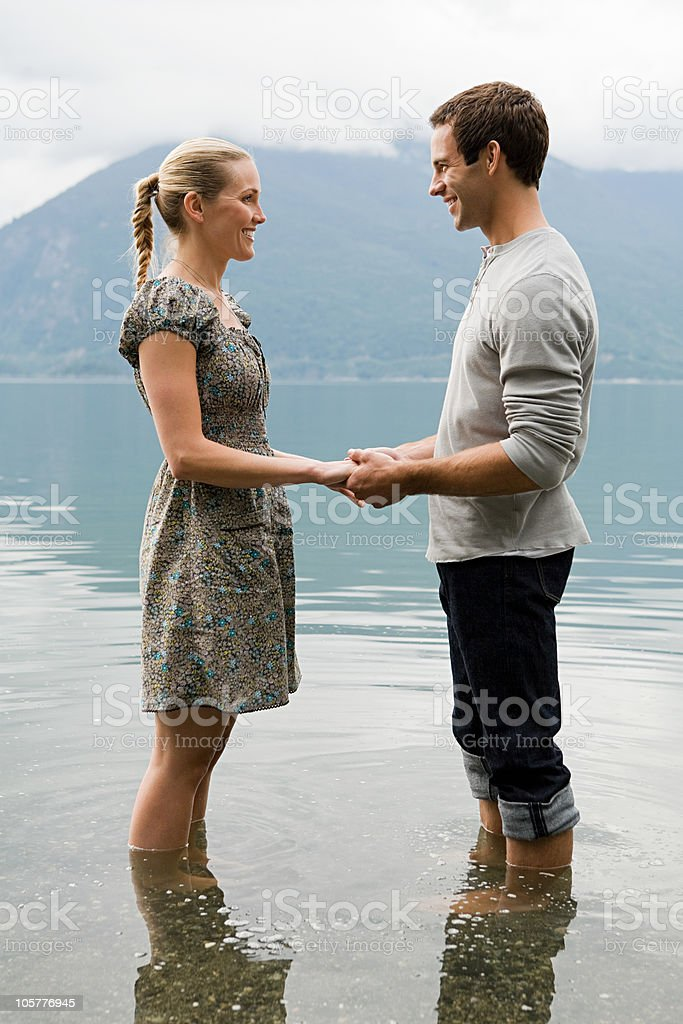 Young couple standing in lake holding hands royalty-free stock photo