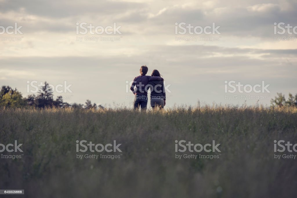 Young couple standing in the field stock photo