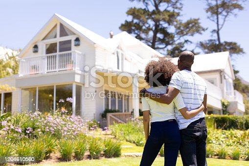 Weekend fun at home together. Rear view of a mixed race couple standing in the garden, embracing and looking at the house