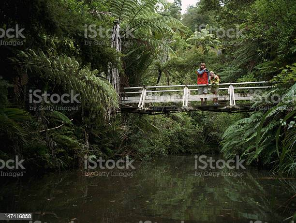 Young Couple Standing On Bridge Stock Photo - Download Image Now