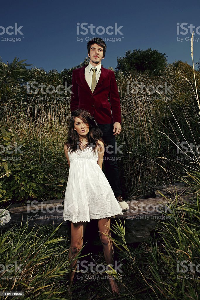 Young Couple Standing on Log in Reeds royalty-free stock photo