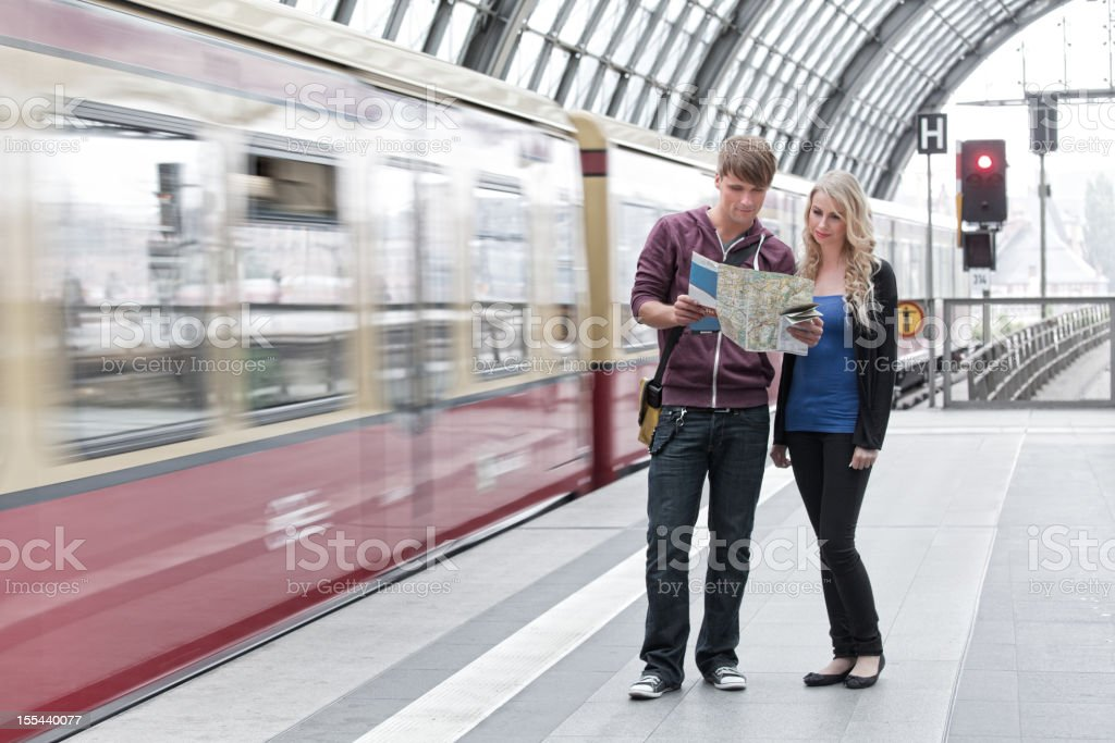 Young couple standing on railroad station platform looking at map