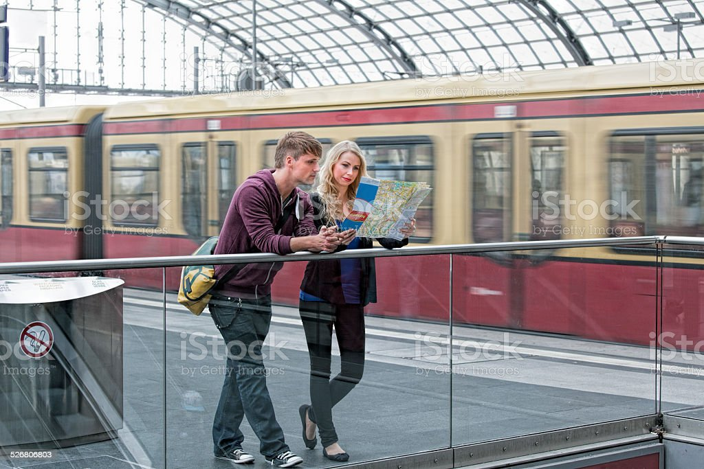 Young couple standing on railroad station platform in Berlin looking...