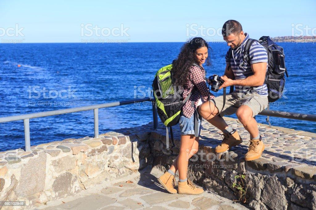 Jeune couple debout sur le quai de la mer - Photo