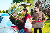 Cheerful young couple came back home from shopping, standing outdoor by the car trunk, the woman holding plastic bags and the man box of vegetables.