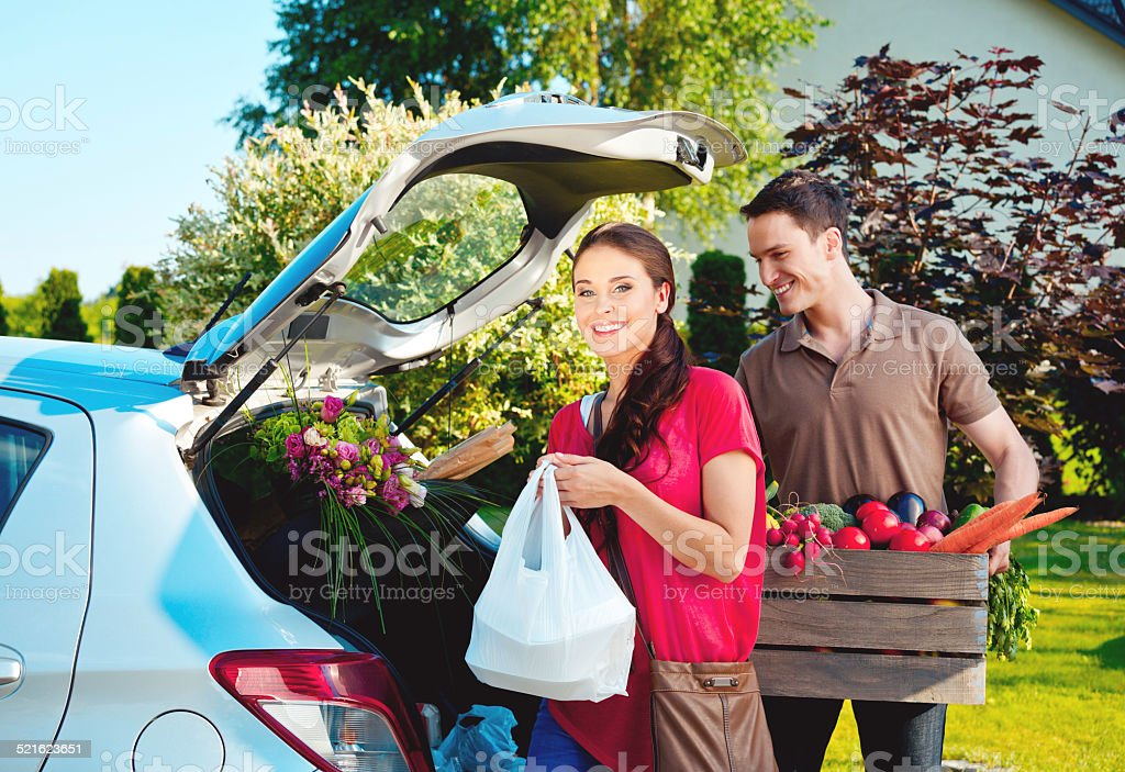 Young couple standing outdoor by car, came back from shopping Cheerful young couple came back home from shopping, standing outdoor by the car trunk, the woman holding plastic bags and the man box of vegetables.  Adult Stock Photo