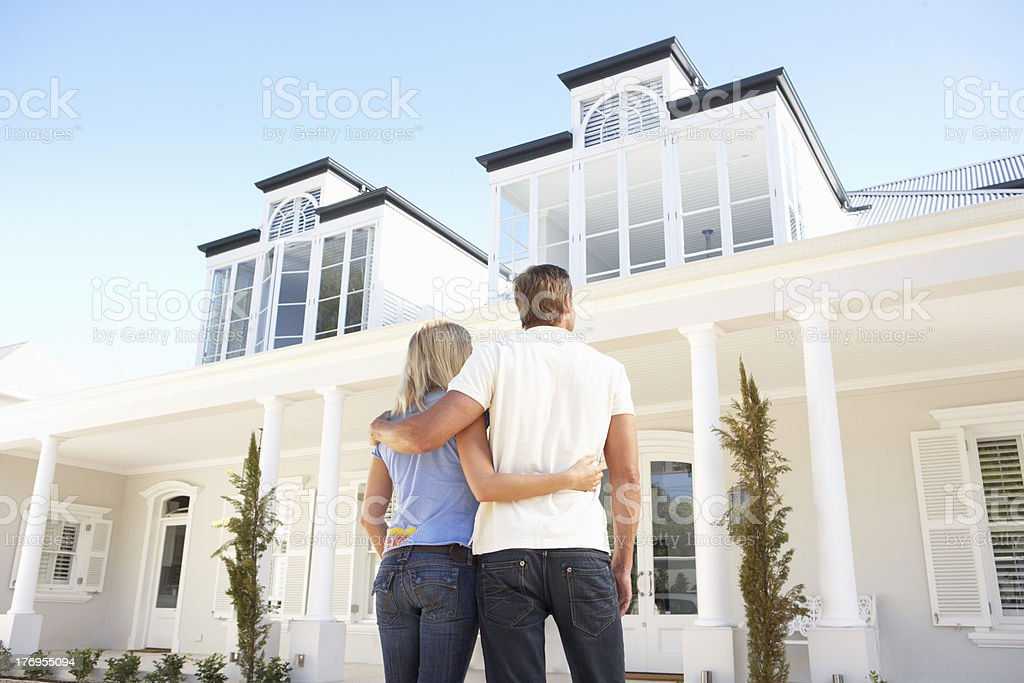 Young Couple Standing Outside Dream Home stock photo