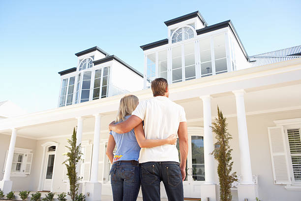 Young Couple Standing Outside Dream Home Young Couple Standing Outside Dream Home model home stock pictures, royalty-free photos & images