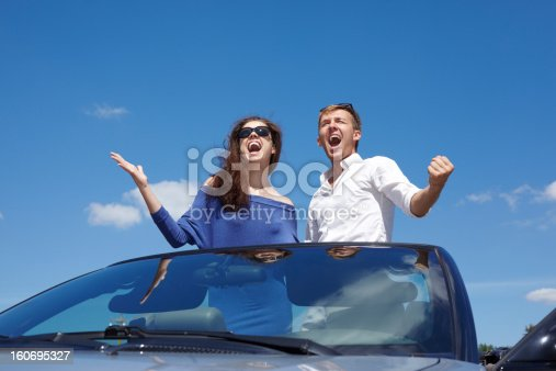 Young couple stands in cabriolet on background of blue sky and shout