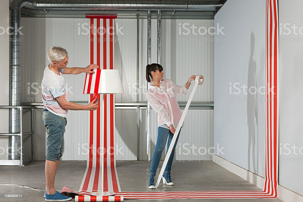 Young couple sticking adhesive tape to wall and lampshade stock photo