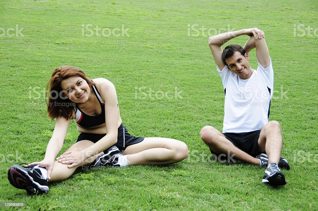 Young Couple Stretching In Park royalty-free stock photo