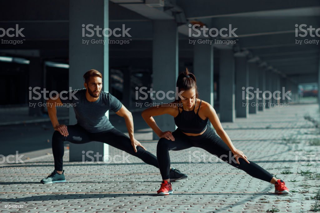 Young couple stretching legs in urban environment stock photo