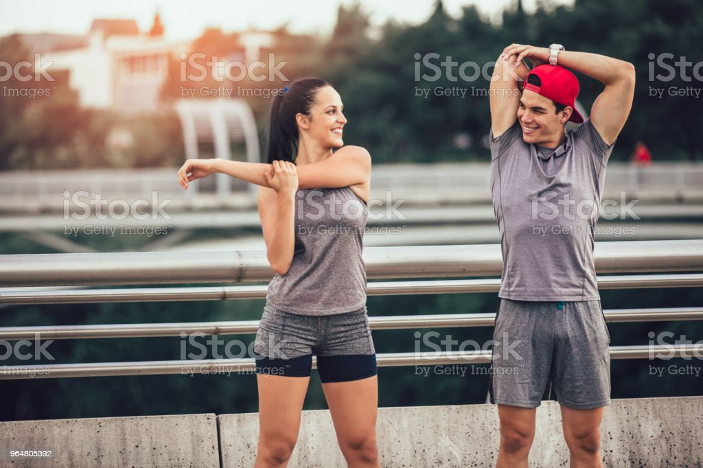 Young couple stretching on the bridge royalty-free stock photo