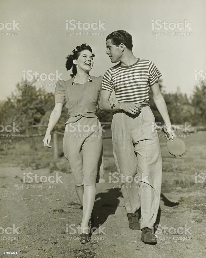 Young couple strolling in field arm in arm, (B&W) stock photo