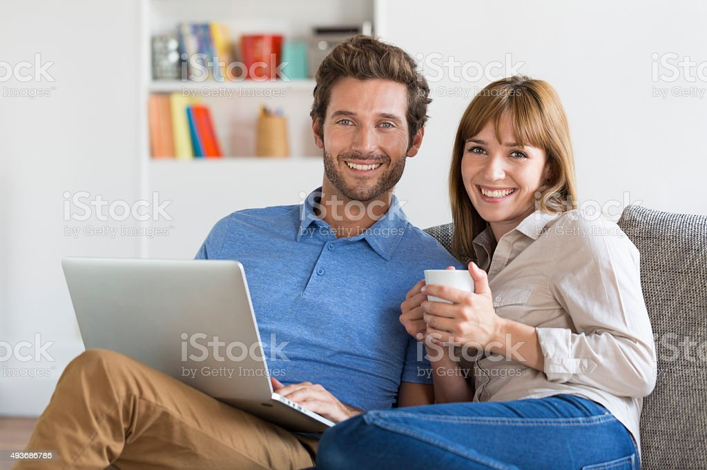 Young couple surfing on internet with laptop. stock photo