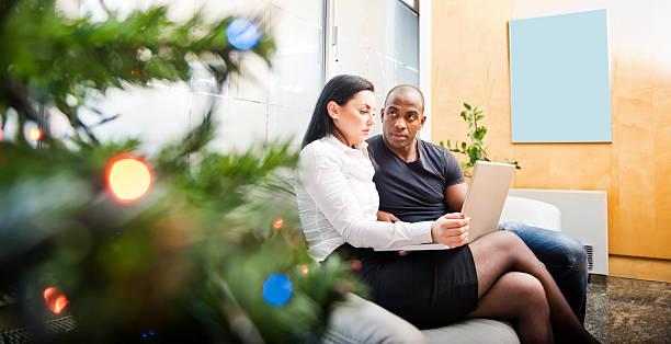 junges paar, surfen im internet auf einem laptop während der feiertage - weihnachtsprogramm stock-fotos und bilder