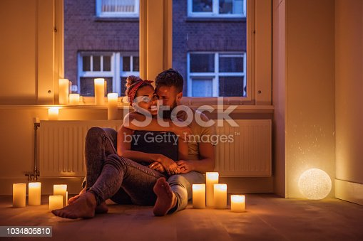 Beautiful young couple enjoying the first night in a new house surrounded by candles
