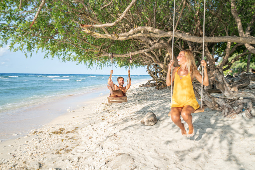 Young couple swinging on beach by the sea, beautiful and idyllic landscape. People travel romance vacations concept.