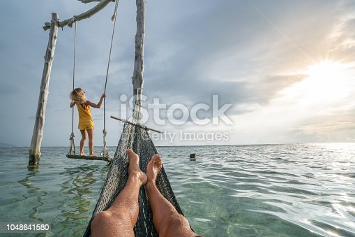 1056198278 istock photo Young couple swinging on the beach by the sea, beautiful and idyllic landscape. People travel romance vacations concept. Personal perspective of man on sea hammock and girlfriend on sea swing. 1048641580