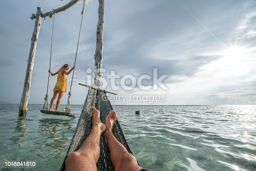 1056198278 istock photo Young couple swinging on the beach by the sea, beautiful and idyllic landscape. People travel romance vacations concept. Personal perspective of man on sea hammock and girlfriend on sea swing. 1048641610