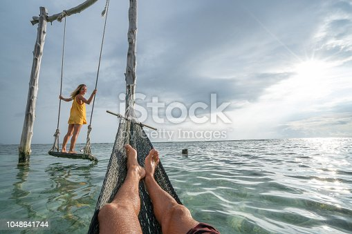 1056198278 istock photo Young couple swinging on the beach by the sea, beautiful and idyllic landscape. People travel romance vacations concept. Personal perspective of man on sea hammock and girlfriend on sea swing. 1048641744