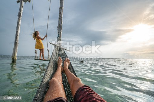 1056198278 istock photo Young couple swinging on the beach by the sea, beautiful and idyllic landscape. People travel romance vacations concept. Personal perspective of man on sea hammock and girlfriend on sea swing. 1048643884