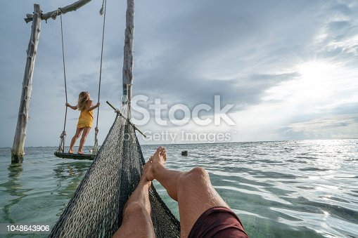 1056198278 istock photo Young couple swinging on the beach by the sea, beautiful and idyllic landscape. People travel romance vacations concept. Personal perspective of man on sea hammock and girlfriend on sea swing. 1048643906