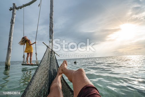 1056198278 istock photo Young couple swinging on the beach by the sea, beautiful and idyllic landscape. People travel romance vacations concept. Personal perspective of man on sea hammock and girlfriend on sea swing. 1048643974
