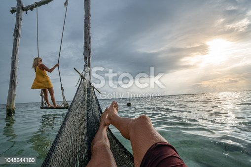 1056198278 istock photo Young couple swinging on the beach by the sea, beautiful and idyllic landscape. People travel romance vacations concept. Personal perspective of man on sea hammock and girlfriend on sea swing. 1048644160