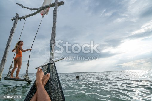 1056198278 istock photo Young couple swinging on the beach by the sea, beautiful and idyllic landscape. People travel romance vacations concept. Personal perspective of man on sea hammock and girlfriend on sea swing. 1048647224