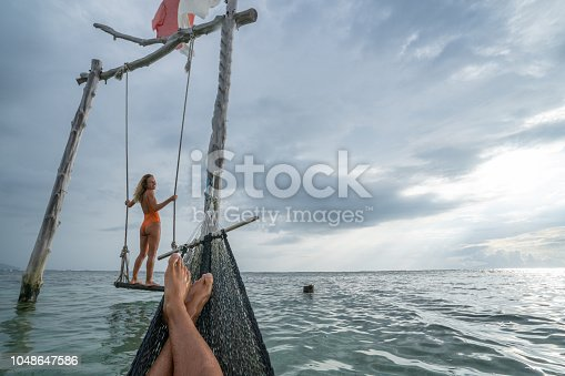 1056198278 istock photo Young couple swinging on the beach by the sea, beautiful and idyllic landscape. People travel romance vacations concept. Personal perspective of man on sea hammock and girlfriend on sea swing. 1048647586
