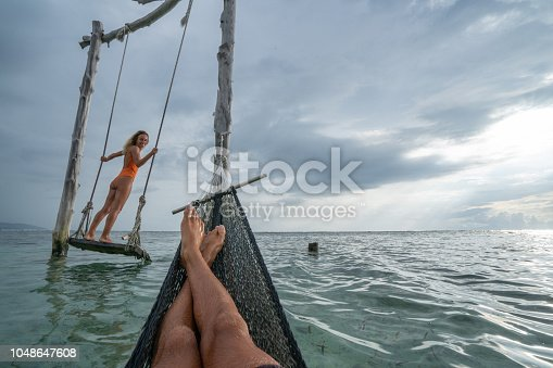 1056198278 istock photo Young couple swinging on the beach by the sea, beautiful and idyllic landscape. People travel romance vacations concept. Personal perspective of man on sea hammock and girlfriend on sea swing. 1048647608