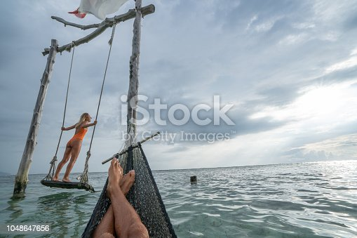 1056198278 istock photo Young couple swinging on the beach by the sea, beautiful and idyllic landscape. People travel romance vacations concept. Personal perspective of man on sea hammock and girlfriend on sea swing. 1048647656