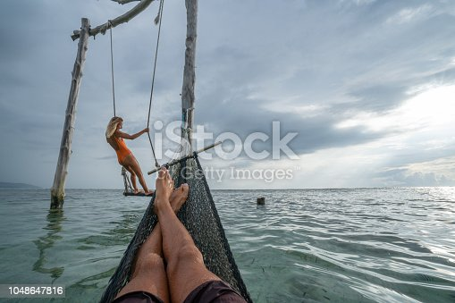 1056198278 istock photo Young couple swinging on the beach by the sea, beautiful and idyllic landscape. People travel romance vacations concept. Personal perspective of man on sea hammock and girlfriend on sea swing. 1048647816