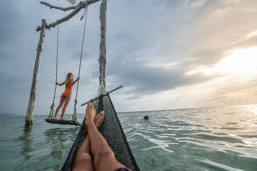 Young couple swinging on the beach by the sea, beautiful and idyllic landscape. People travel romance vacations concept.\nPersonal perspective of man on sea hammock and girlfriend on sea swing.