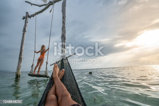 1056198278 istock photo Young couple swinging on the beach by the sea, beautiful and idyllic landscape. People travel romance vacations concept. Personal perspective of man on sea hammock and girlfriend on sea swing. 1048648252